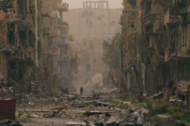 A child walks in the ruins of Deir-al-Zor, eastern Syria. Cred: Reuters