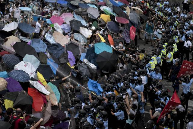 Clash between umbrella-holding protestors and police. September 28, 2014. Alex Ogle/AFP