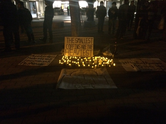 Signs and candles lie outside Geisel Library on UCSD campus